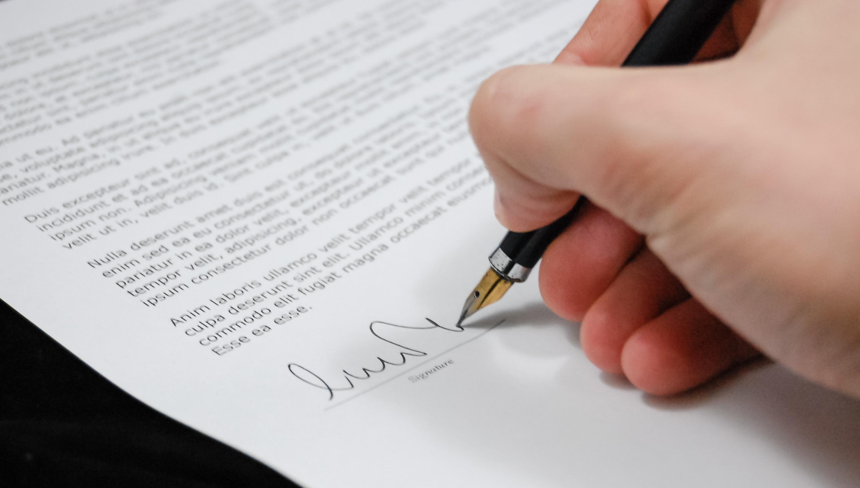 書類へサインしている写真