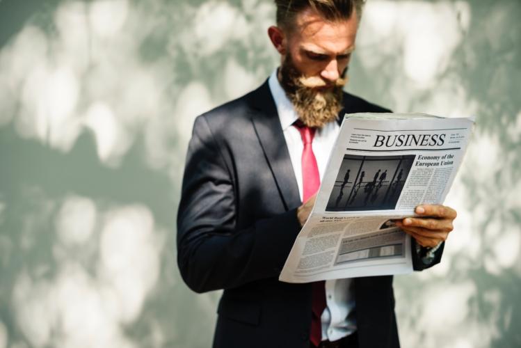 新聞を読みながら歩いている男性の写真