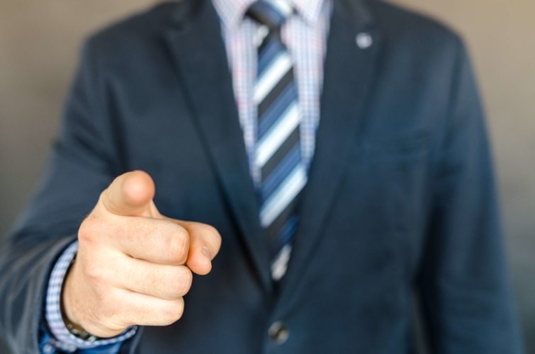 右手の人差し指で指差しているビジネスマンの写真